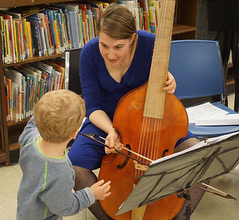 Sarah Stone showing her viola da gamba to a child in a library