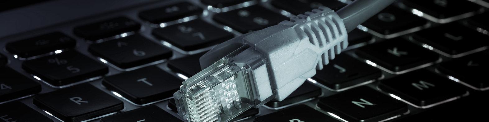 """Headerbild der Stellenanzeige """"Systemadministration"""" bei der IT-Firma TECXIPIO in Karlsruhe. Auf dem Bild erkennt man ein Netzwerkkabel, das auf einer Tastatur liegt"""