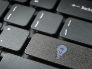 """Tastatur eines Computers, auf welcher eine blaue Glühbirne zu sehen ist. Ein Textfeld in der Mitte des Bildes verweist auf die Job Seite """"Software Developement"""" des IT-Unternehmens TECXIPIO in Karlsruhe"""