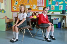 School children sitting on low chairs