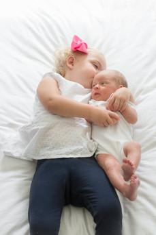 Rye NY New York Jo Bryan JoBryan photo photography photos portrait inside sisters baby girl bow blue white pink lying down reclining happy