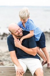 Jo Bryan Photography Rye New York NY family father son beach fence water hugging blue shirts smiling