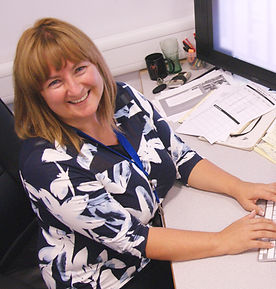 Principal Sarah Holmes-Carne, smiling at her desk.