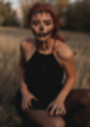 Model sitting in field with a black dress and face paint on