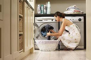 woman-loading-washing-machine-in-kitchen