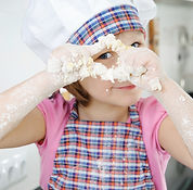 Little girl in hat and apron cooking in