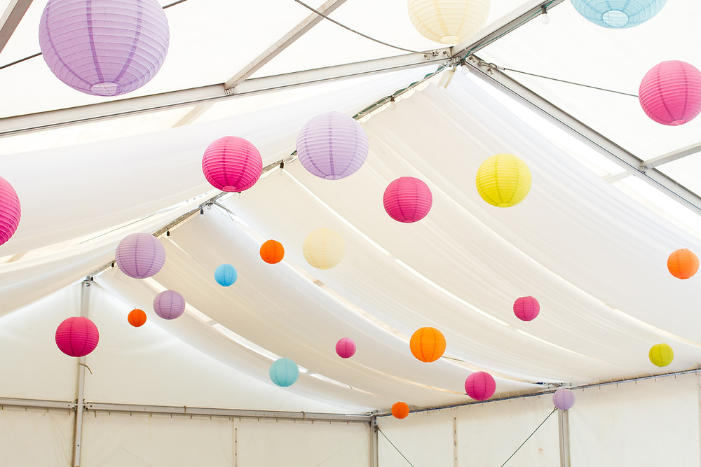 Colored paper lanterns hanging in white tent