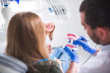 dentist-holding-teeth-model-near-female-
