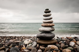 A balanced stack of 9 stones on a stony beach - water to horizon.