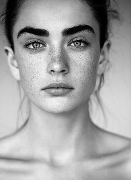 Svartvitt porträtt av kvinna med fräknar