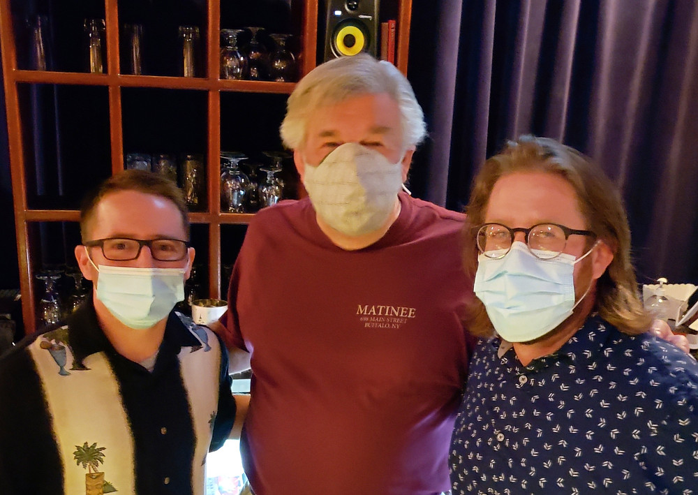 three men in covid masks pose for the camera