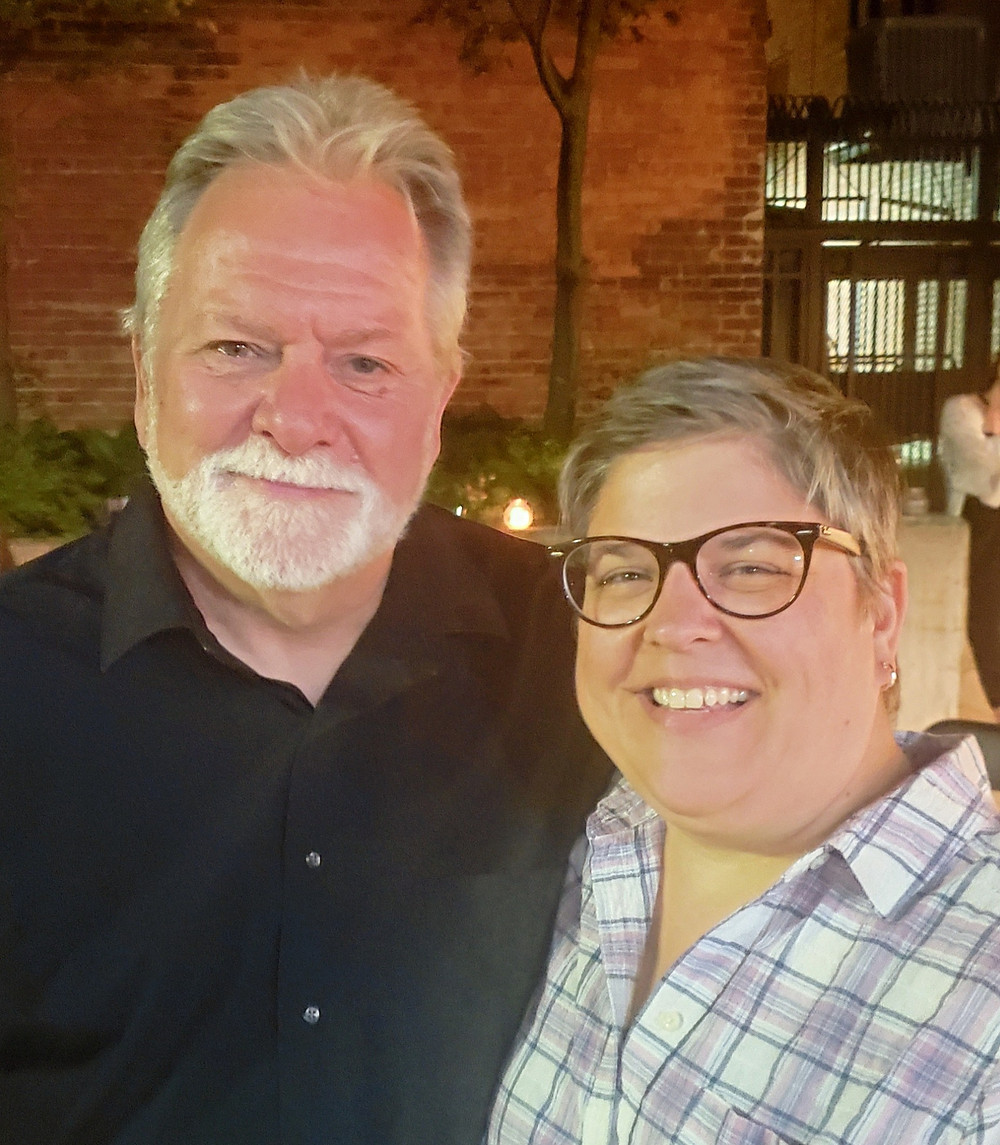 a man with a beard and a woman with glasses smile for the camera