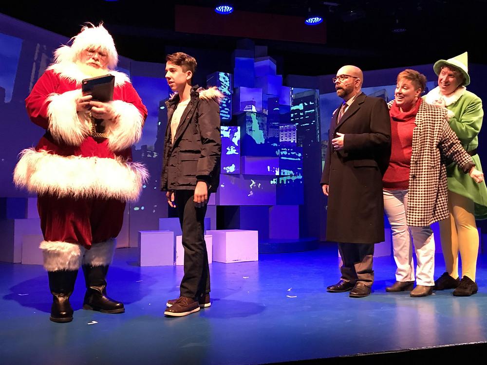 Nicholas Lama as Santa Claus, Johnny Kiener as Michael Hobbs, Louis Colaiacovo as Walter Hobbs, Jennifer Mysliwy as Emily Hobbs, and Chris J. Handley as Buddy the Elf. Photo by Doug Weyand