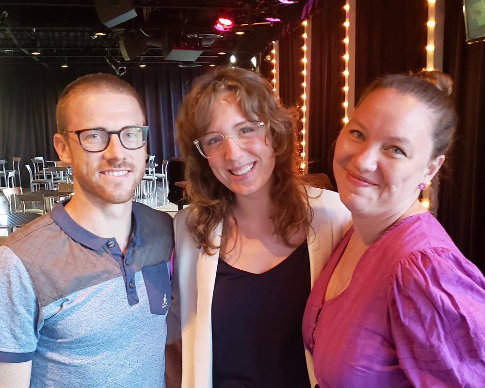 three happy people in front of a cabaret stage