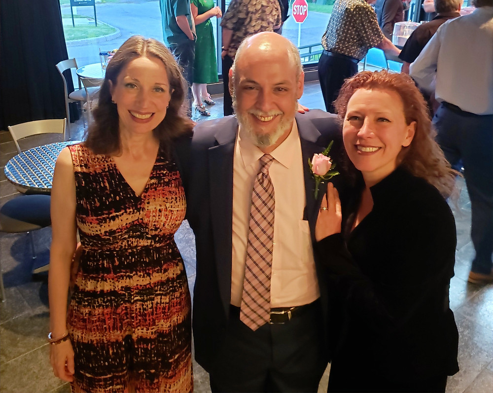 Three smiling people at an opening night party
