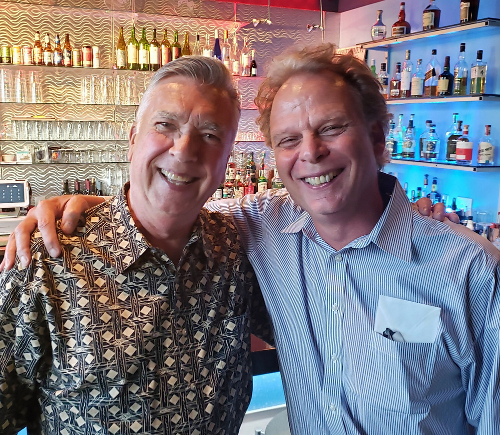 two men smiling in front of a theater lobby bar