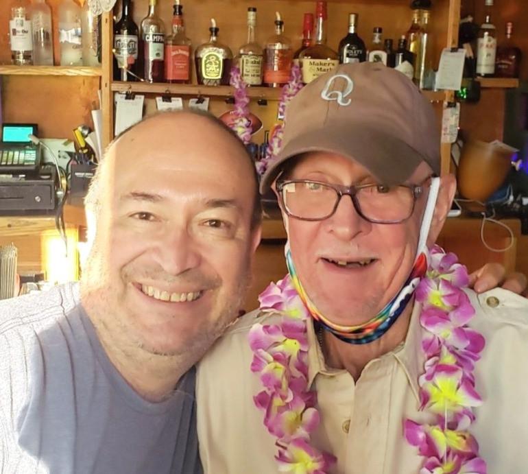 two men smiling, one wearing a baseball cap and an Hawaiian Lei