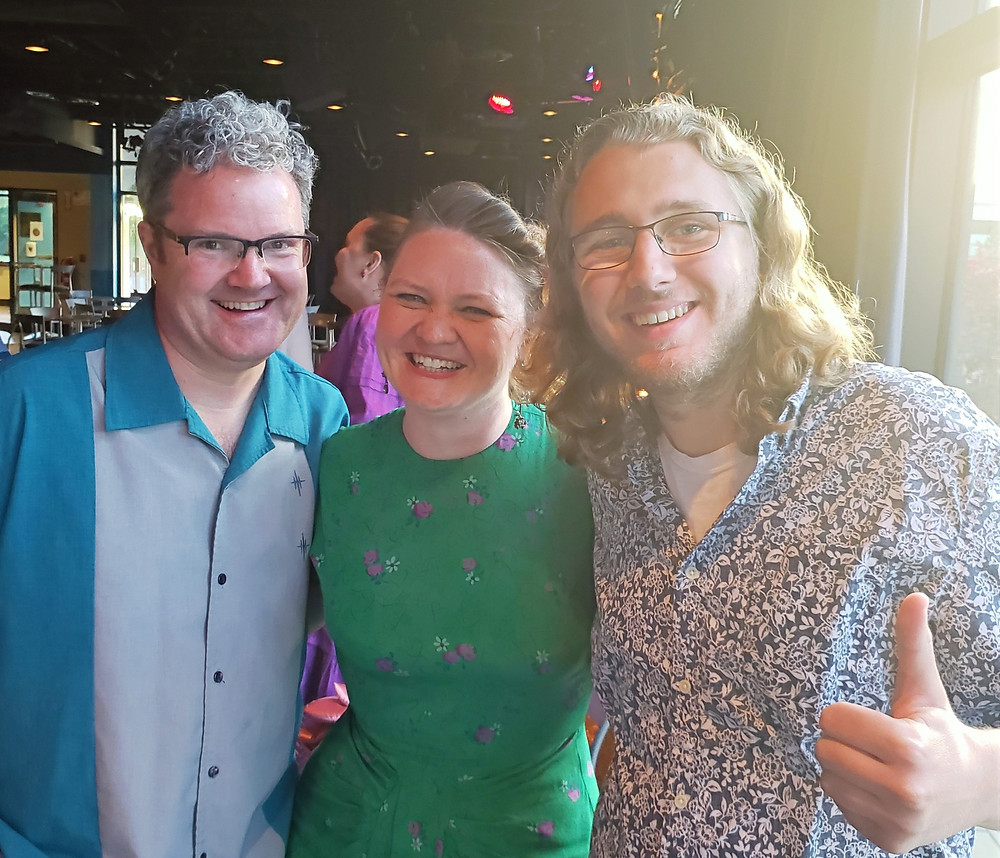 three happy people at an opening night party