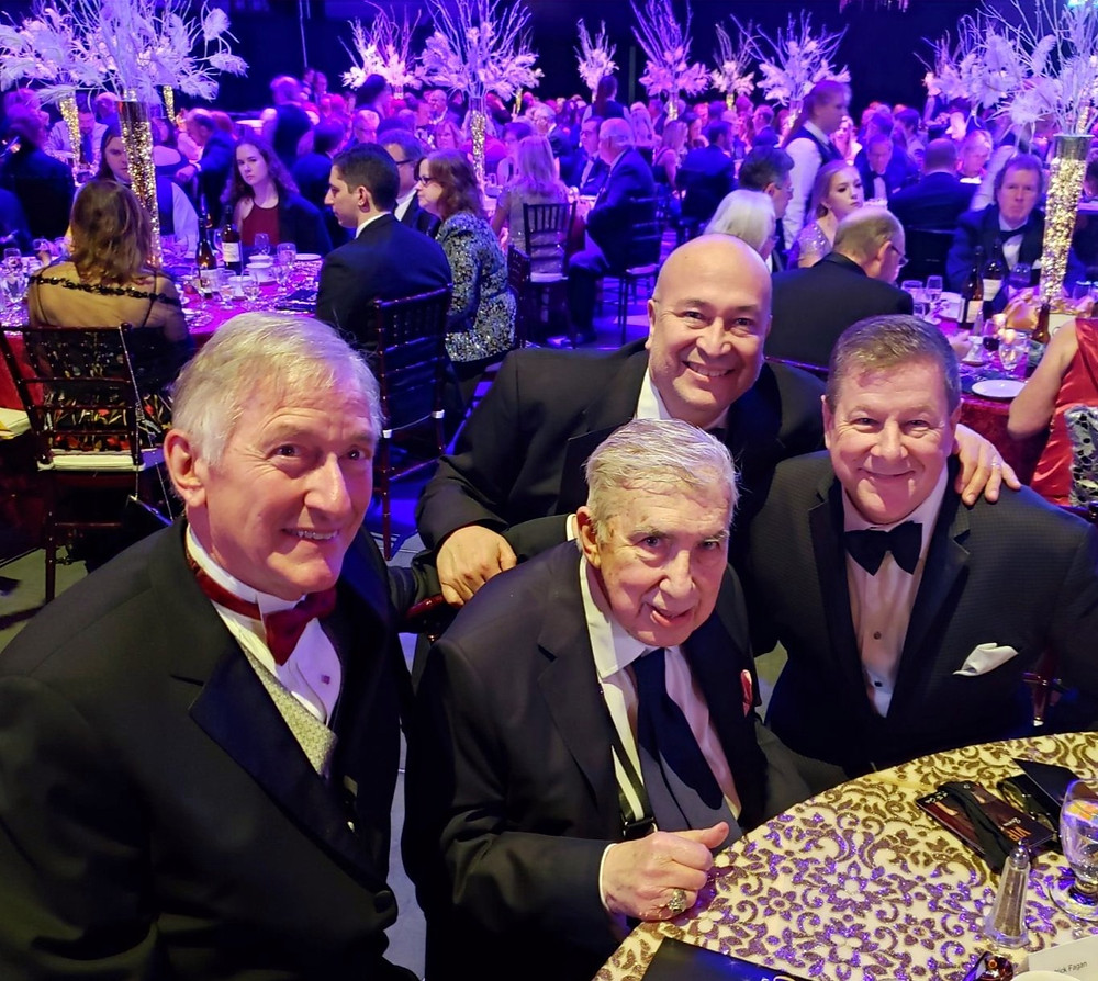 four men in tuxedos posing for the camera at a gala dining table.