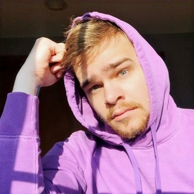 Daniel Mertzlufft, a young man with a beard wearing a lavender colored hoodie sweatshirt