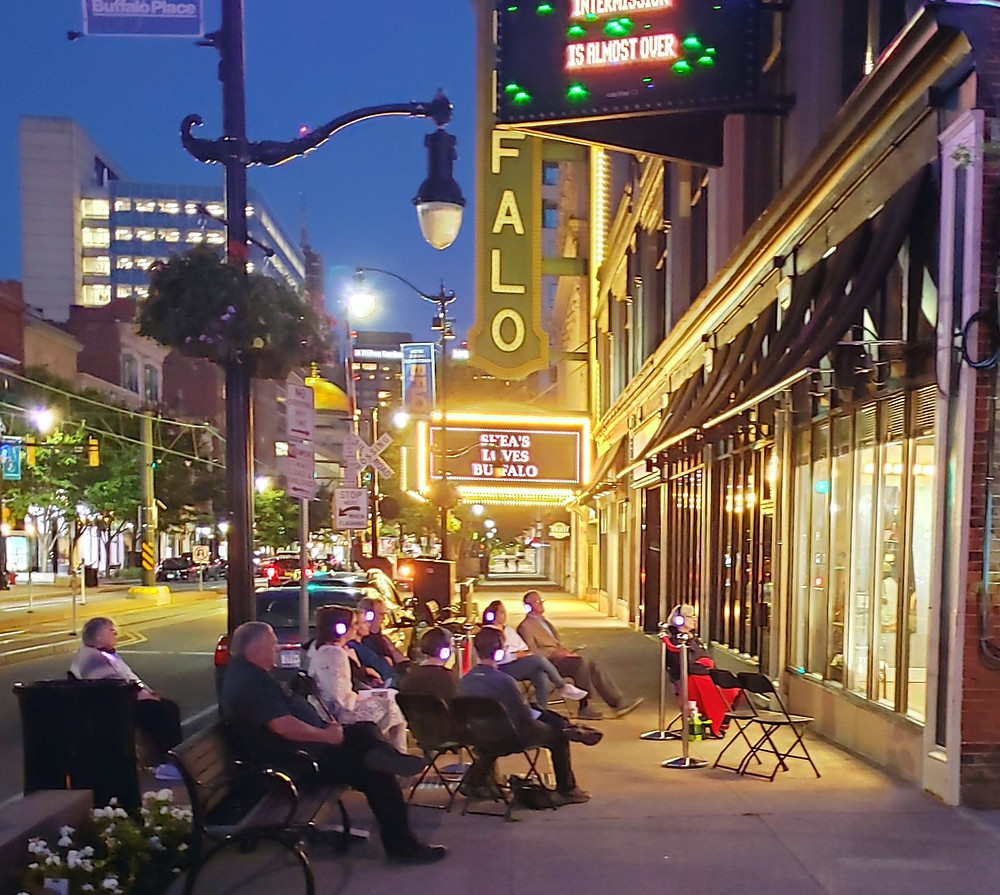 An audience sits outdoors at night watching a play through a storefront window with city lights in the background
