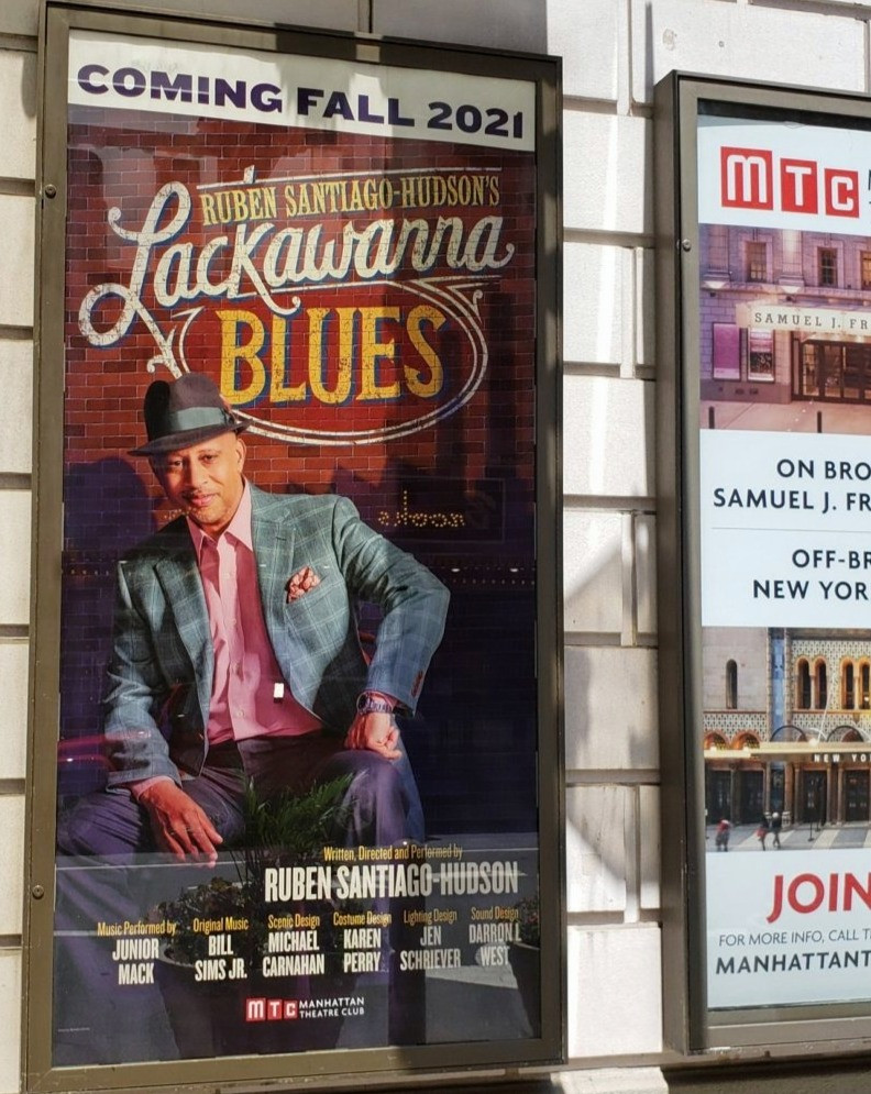 """Poster for Ruben Santiago-Hudson's """"Lackwanna Blues"""" on Broadway in New York City.  He is wearing a pink shirt, a checkered sports jacket, and a fedora."""