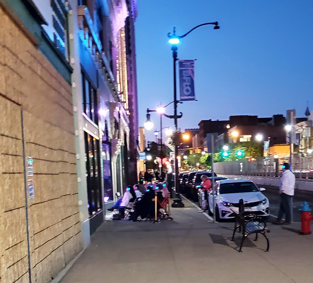 an audience sitting on a sidewalk on a city street at night, watching a play through a storefront window, beneath the street lights