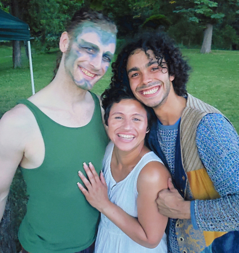Three actors in a park. One is a tall man with fairy makeup on his face; one is a smaller woman, and one is a curly haired man.