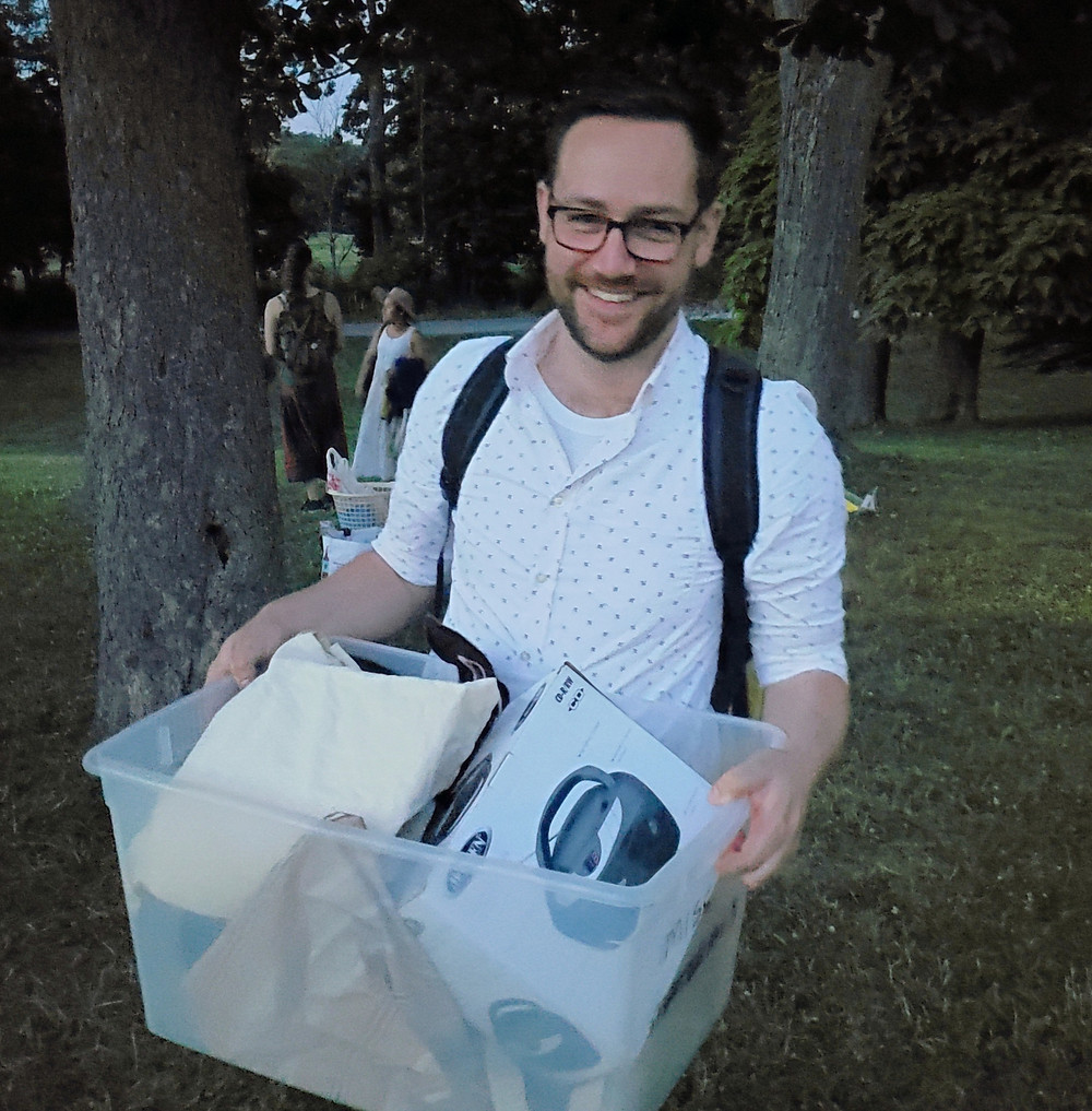 A young man with a beard and glasses stands in a park, carrying a box of stuff