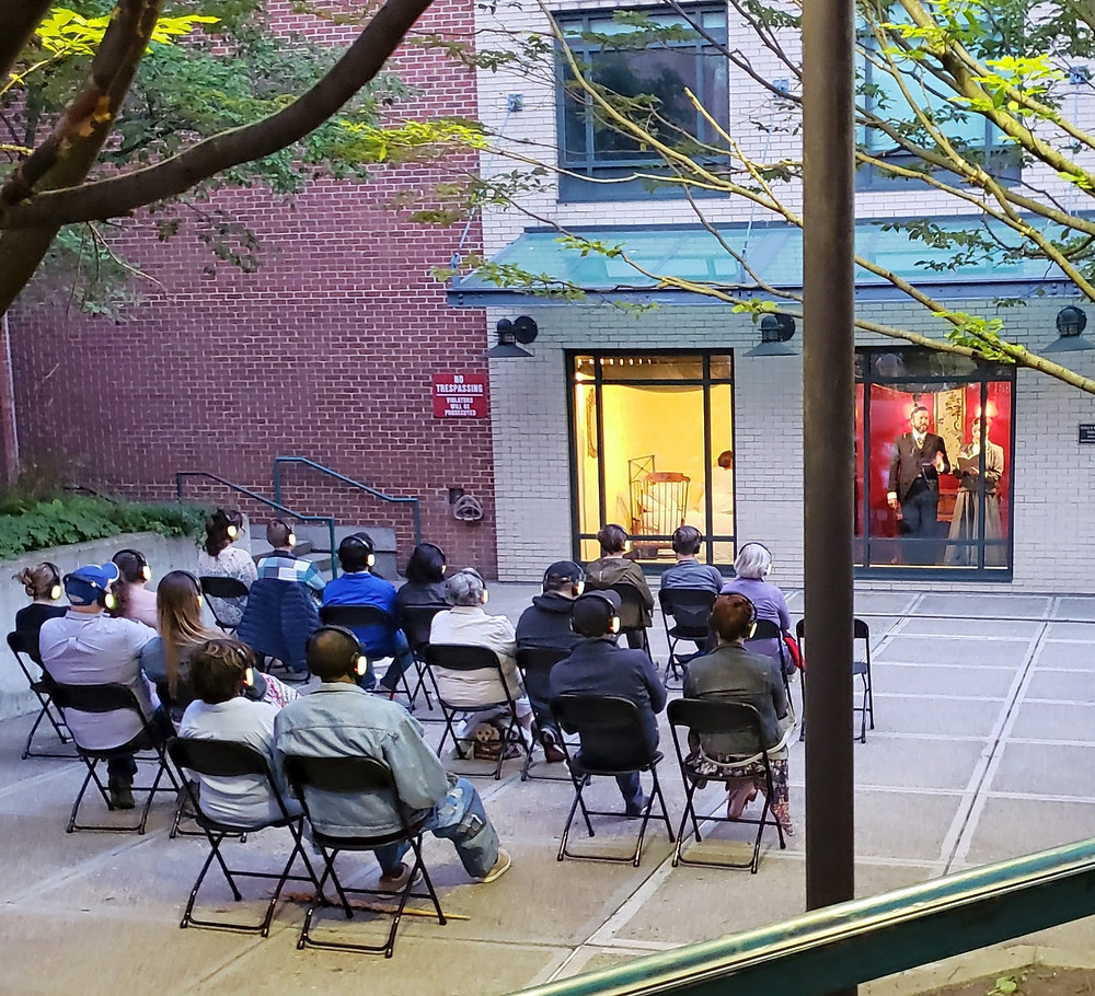 people in folding chairs watching a play through the windows of a building