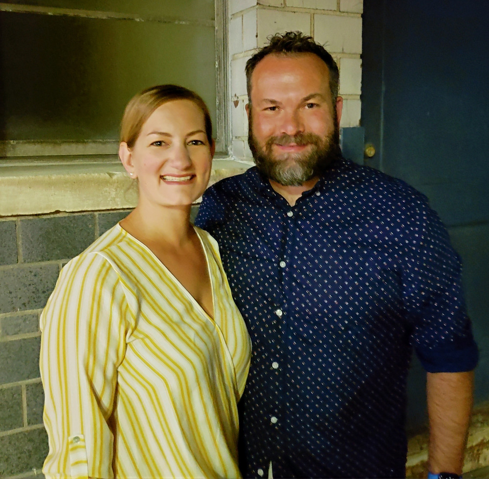 A woman in a yellow striped outfit with a bearded man in a blue patterned button downshirt