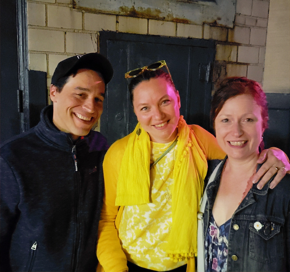 a man and two women smiling for the camera in front of a white glazed block wall