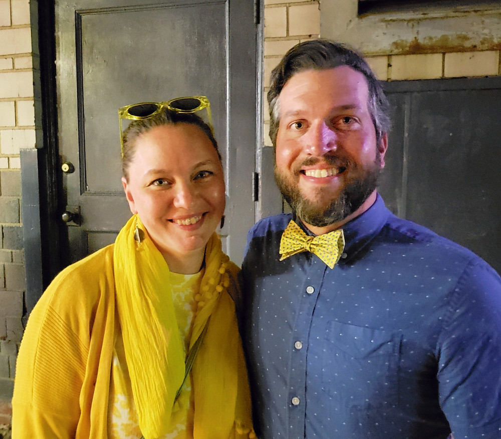 A woman with sunglasses on her head, with a bearded man wearing a bowtie