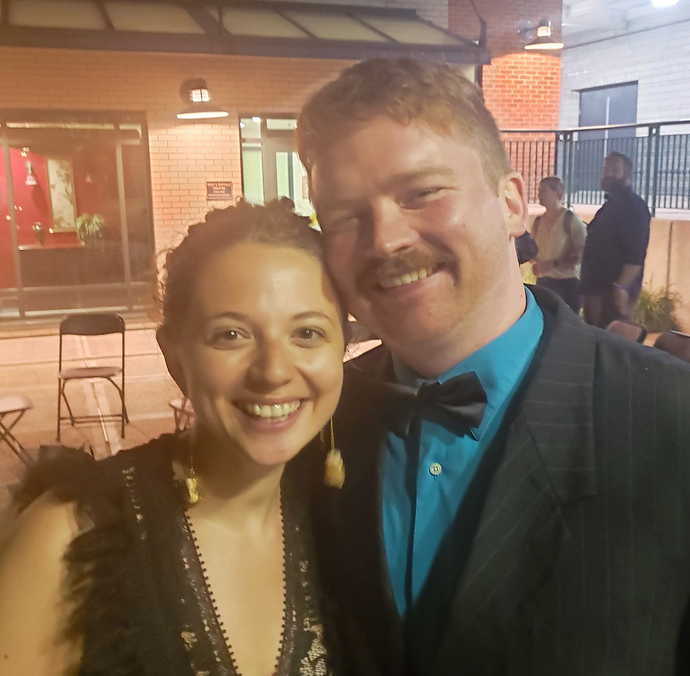 a woman and a man in evening clothes at an outdoor patio party