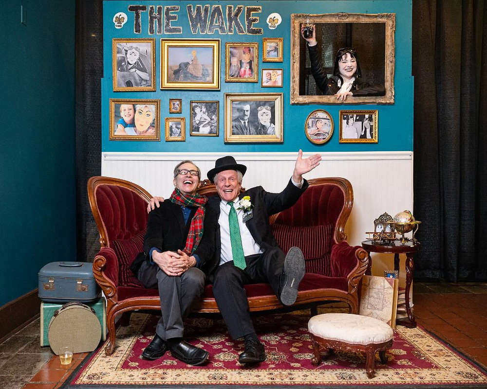 """Anthony Chase with Vincent O'Neill at """"The Wake"""" in front of a wall with an actress in a picture frame."""