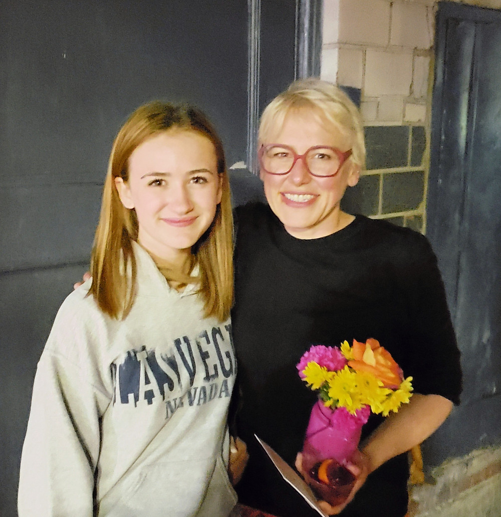 A teenage girl in a white Las Vegas sweatshirt with a woman in a black shirt holding flower and a card, smiling for the camera
