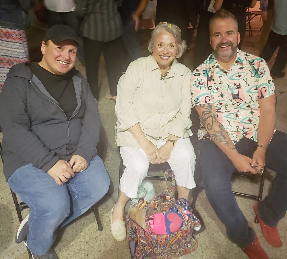 Three people sitting in chairs and smiling for the camera