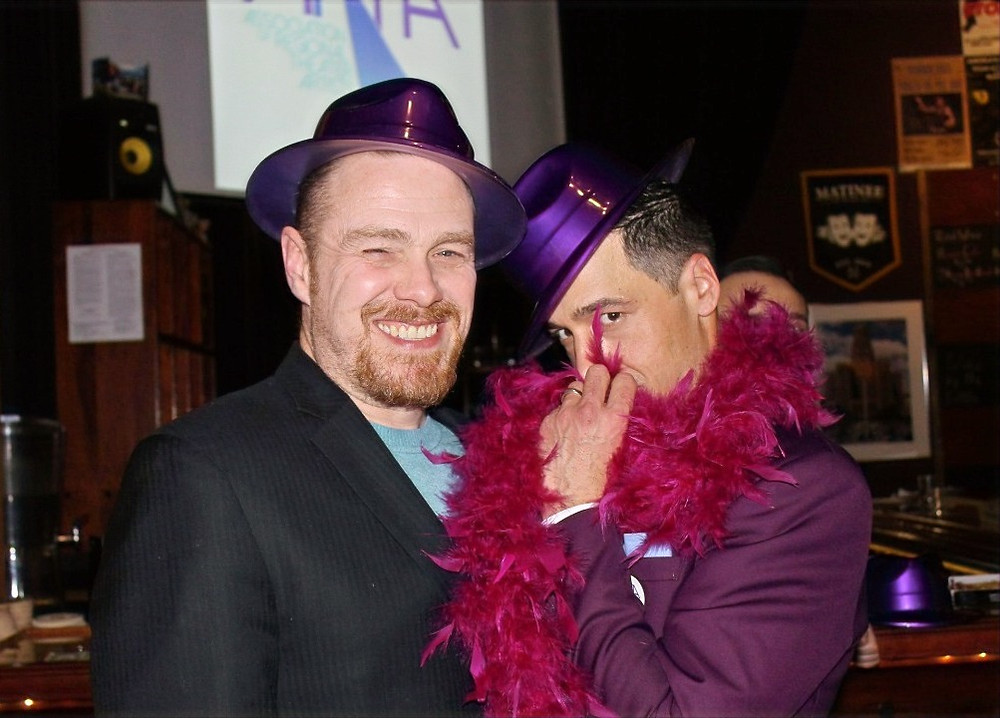 Chris Kelly and Ben Michael Moran wearing purple hats and a purple boa