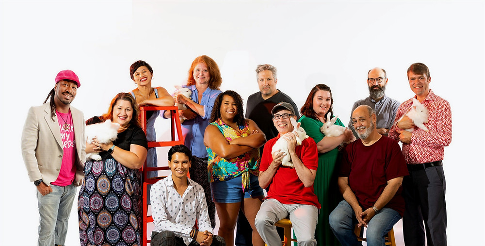 12 actors posing with white rabbits and a red ladder
