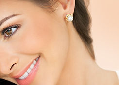 Beautiful smiling young woman with long hair and pearl earrings studs over warm beige back