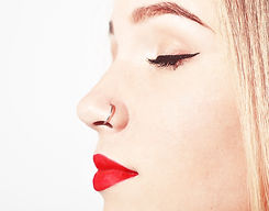 Closeup of a young woman's visage with piercing hanging from her nose.  Beauty Teenager Gi
