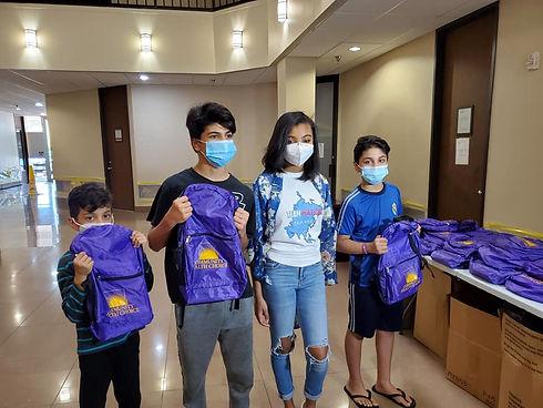 Saniya Symone giving students packpacks.