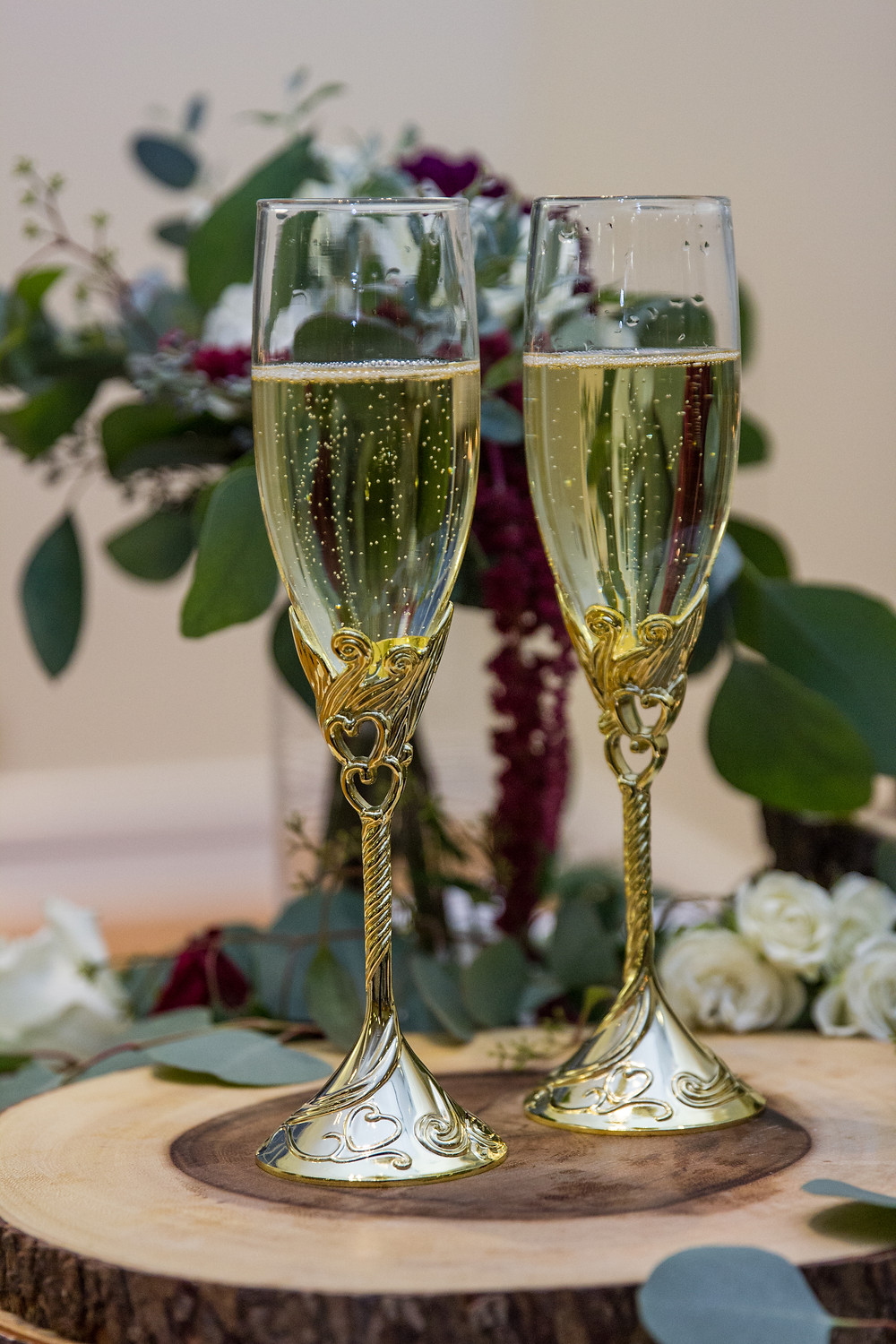 champagne toast, wedding photography, photographer, flutes, champagne, columbia mo, missouri, greenery, burgundy, wood, wedding inspiration