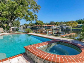 Windows and French doors across the back of the home lead out to a dazzling saltwater pool and paver patio.