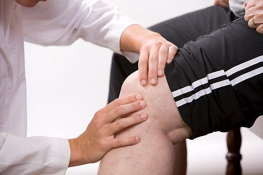 bigstock-Physical-Therapist-Checks-A-Kn-