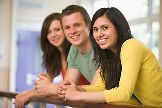 three-college-students-leaning-on-banist