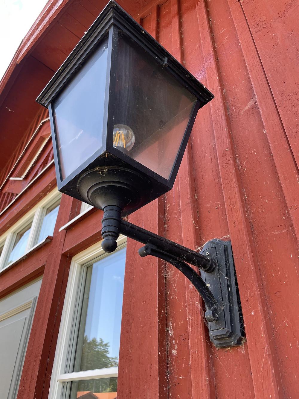 En lampa på en röd fasad med spindelnät.