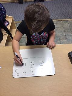 raelyn writing numerals.jpg