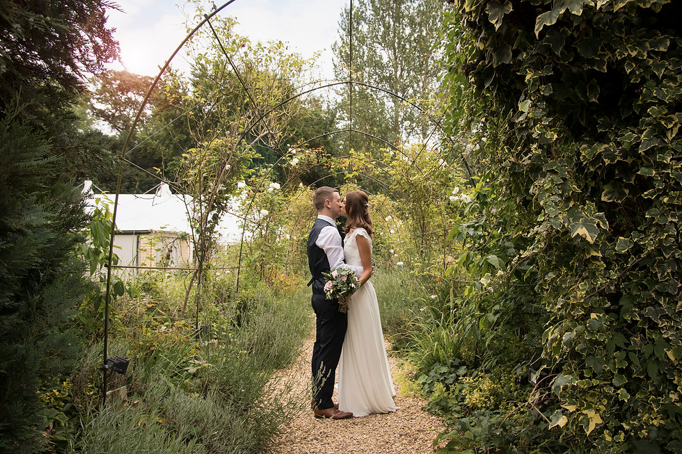A couple on their wedding day kissing under a leafy archway