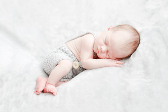 Newborn baby in grey dungarees on a white background